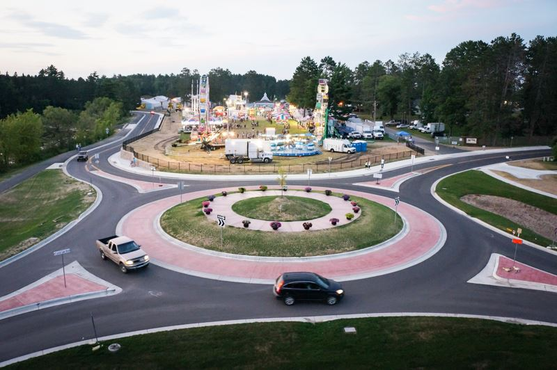 Image of two cars driving the Fairgrounds Roundabout with the Fair Viewable in the Rear